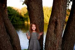 Dziecko jest 4 lat z niebieskimi oczami i małymi kędziorami, Stojaki blisko wielkiego drzewa obok wody Dziecka ` s przyjemność Zdjęcia Stock