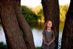 Dziecko jest 4 lat z niebieskimi oczami i małymi kędziorami, Stojaki blisko wielkiego drzewa obok wody Dziecka ` s przyjemność Fotografia Royalty Free