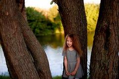 Dziecko jest 4 lat z niebieskimi oczami i małymi kędziorami, Stojaki blisko wielkiego drzewa obok wody Dziecka ` s przyjemność Fotografia Stock