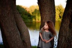 Dziecko jest 4 lat z niebieskimi oczami i małymi kędziorami, Stojaki blisko wielkiego drzewa obok wody Dziecka ` s przyjemność Zdjęcia Royalty Free