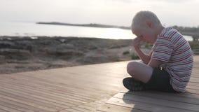 Dziecko jest smutny przy zmierzchem morzem zbiory