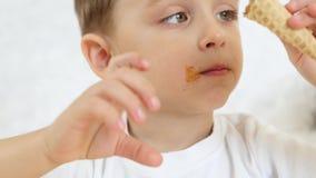 Dziecko jest szczęśliwy jeść czekoladowego rożek lody w gofra rożku, siedzi przy stołem na białym tle, ostrość zbiory