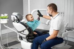 Dziecko jest szczęśliwy po stomatologicznego traktowania i dawać jego lekarka w nowożytnej białej stomatologicznej klinice wysoko Zdjęcie Stock