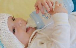 Dziecko jest uśmiechnięty i bawić się z butelką Zdjęcia Royalty Free