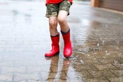 Dziecko jest ubranym czerwonych podeszczowych buty skacze w kałużę fotografia royalty free