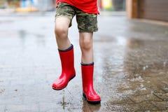 Dziecko jest ubranym czerwonych podeszczowych buty skacze w kałużę fotografia stock