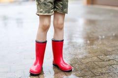Dziecko jest ubranym czerwonych podeszczowych buty skacze w kałużę z bliska Dzieciak ma zabawę z chełbotaniem z wodą Ciepły ciężk obraz royalty free