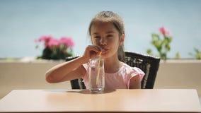 Dziecko jest wodą pitną w restauraci która lokalizuje na brzeg zbiory