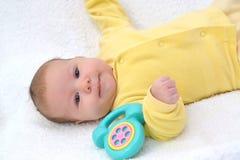 Dziecko kłama z zabawkarskim telefonem na białym tle Zdjęcie Royalty Free