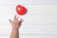 Dziecko kochający wręcza dawać czerwonemu sercu na białym drewnianym tle obraz stock