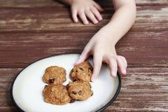 Dziecko kraść dyniowego czekoladowego układu scalonego ciastko od talerza Zdjęcia Stock