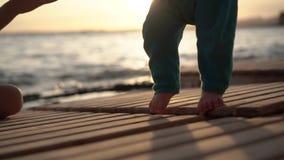 Dziecko małe nogi stemplują na sunbeds podczas zmierzchu przy morzem w zwolnionym tempie zdjęcie wideo
