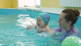 Dziecko ma zabawę w basenie z pływackim instruktorem zbiory