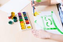 Dziecko maluje jaskrawego - zielony dom z uśmiechem pojęcie ekologia Szkolny przydział lub twórczość zdjęcia royalty free
