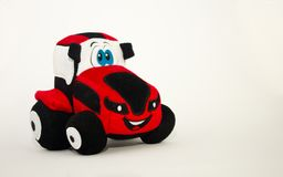 Dziecko miękki śliczny zabawkarski czerwony ciągnik na białym tle obraz stock
