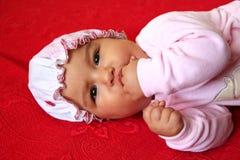 Dziecko na czerwonym łóżku Fotografia Royalty Free