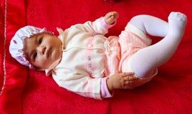 Dziecko na czerwonym łóżku Zdjęcia Royalty Free