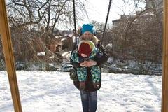 Dziecko na huśtawce w zimie Zdjęcia Royalty Free