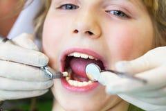 Dziecko na przyjęciu przy dentysty przyjęciem przy dentistClose w górę portreta uśmiechać się dziewczyny przy dentystą troszkę fotografia royalty free