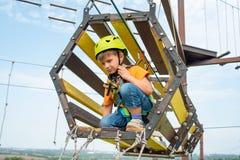 Dziecko na wagonie kolei linowej w krańcowym parku Chłopiec ubierająca w ochronnym ubezpieczeniu i hełmie, pokonuje przeszkody w  zdjęcie stock
