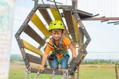 Dziecko na wagonie kolei linowej w krańcowym parku Chłopiec ubierająca w ochronnym ubezpieczeniu i hełmie, pokonuje przeszkody w  zdjęcie royalty free