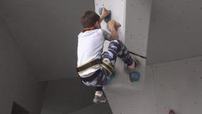 Dziecko na wspinaczkowej ścianie Mała chłopiec wspina się głaz w mountaineering szkoleniu Dziecko angażuje w zdjęcie wideo