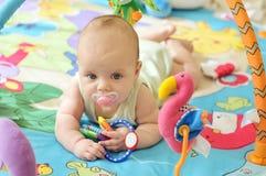 Dziecko na zabawkarskim dywaniku Zdjęcia Royalty Free