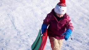 Dziecko na zima spacerze Dziewczyna jedzie od śnieżnego obruszenia na plastikowym talerzu zbiory