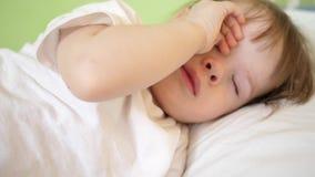 Dziecko naciera oczy spać próby i Mały dziecko spada uśpiony w jego ściąga zbiory
