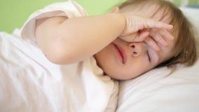 Dziecko naciera oczy spać próby i Mały dziecko spada uśpiony w jego ściąga zdjęcia stock