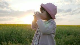 Dziecko napojów woda, śliczny żeński dziewczyna portret, dziecka ` s ręki trzyma szklaną czystą czystą wodę na zmierzch naturze,  zbiory wideo