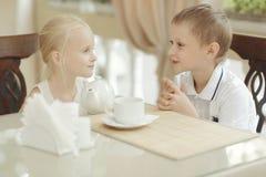 Dziecko napoju herbata w kawiarni obraz stock