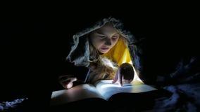 Dziecko nastoletnia i psia czytelnicza dziewczyna czyta książkę przy nocą z latarka dzieciaka lying on the beach pod koc zbiory wideo