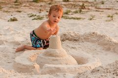 Dziecko niszczy piaska kasztel obraz stock