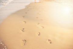 Dziecko odciski stopy w piasku Ludzcy odciski stopy prowadzi zdala od widza Rząd odciski stopy w piasku na plaży w Zdjęcie Royalty Free