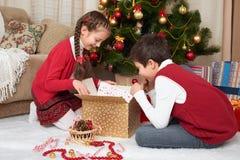 Dziecko odpakowywa prezentów pudełka blisko choinki, dekoracja w domu, szczęśliwa emocja, zima wakacje pojęcie Zdjęcia Royalty Free