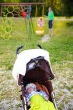 Dziecko odpoczywa w spacerowiczu na boisku obraz royalty free