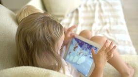 Dziecko ogląda ang używać pastylkę w domu Dzieci używa nowożytnego laplop, pastylka na kanapie Mała dziewczynka bawić się na zbiory wideo