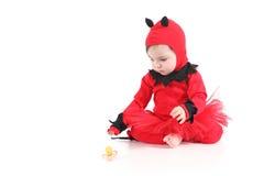 Dziecko ogląda pacyfikator z czerwonym demonu przebraniem obraz royalty free