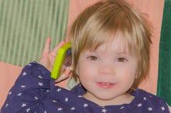 Dziecko opowiada na zabawkarskim telefonie fotografia royalty free