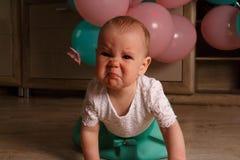 Dziecko płacze, dostają gniewnymi, siedzą na, troszkę dziewczyna, dziecko podłoga marszczących jej nos płaczach i, blisko balonów obrazy stock