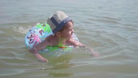 Dziecko pływa na nadmuchiwanym okręgu w morzu szczęśliwego dzieciństwa pozytywne emocje zbiory