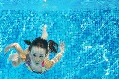 Dziecko pływa w basenie podwodnym, szczęśliwa aktywna dziewczyna nurkuje zabawę i pod wodą, dzieciak sprawnością fizyczną i sport obraz stock