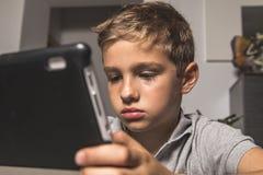 Dziecko patrzeje pastylkę W średnim wieku chłopiec fotografia royalty free