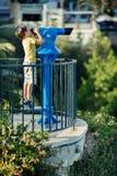 Dziecko patrzeje przez monety działać lornetek Zdjęcia Stock