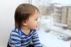 Dziecko patrzeje z okno Obrazy Royalty Free