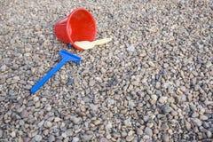 Dziecko piaska zabawki nad kamienistym boiskiem Obrazy Stock