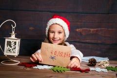 Dziecko pisze liście Święty Mikołaj W Santa kapeluszu śmieszna dziewczyna pisze liście Santa Zdjęcie Stock