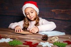 Dziecko pisze liście Święty Mikołaj W Santa kapeluszu śmieszna dziewczyna pisze liście Santa Zdjęcia Royalty Free