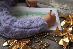 Dziecko pisze liście Santa i rysuje choinki Złoci Bożenarodzeniowi koraliki i złociści tasiemkowi łęki na drewnianym Zdjęcia Stock